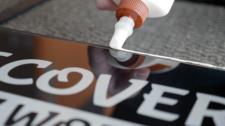 Applying glue to the exposed front edges of the sign box.